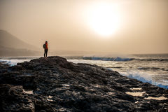 Male silhouette on the rocky ocean coast. In foggy weather Stock Photo
