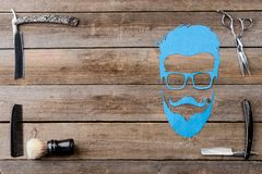 Male silhouette and scissors. Scissors, a brush, a male silhouette, straight razors and a comb on the wooden background, close-up. Place to insert your text. For Royalty Free Stock Images