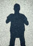 Male silhouette in shadow on asphalt. The shape of a male silhouette. Shade on asphalt. Gray asphalt texture background. Mobile photo Royalty Free Stock Image