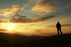 Male silhouette on sunrise. Male on the sunrise in mountain Stock Image