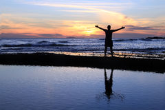 Male silhouette at sunset. Silhouette of a man with outstretched arms at sunset on a beach Royalty Free Stock Photos