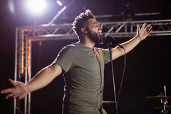 Male singer with arms outstretched performing at nightclub. Low angle view of male singer with arms outstretched performing at nightclub during music festival Royalty Free Stock Photos