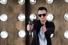 Male singer in black with microphone performs in projectors ligh. Male singer of rock or pop music dressed in black and sunglasses with microphone performs on Stock Photos