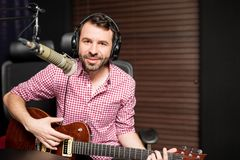 Male singer broadcasting a song live at radio station. Handsome young male singer playing guitar and singing in microphone at radio station Royalty Free Stock Photo