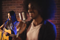 Male singer with female guitarist in nightclub. Close up of male singer with female guitarist in nightclub Royalty Free Stock Photos