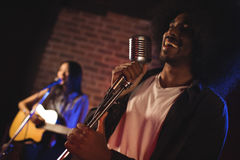 Male singer with female guitarist performing in nightclub. Cheerful male singer with female guitarist performing in nightclub Royalty Free Stock Images