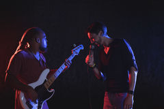 Male singer with guitarist performing at music concert. Young male singer with guitarist performing at music concert Royalty Free Stock Photography