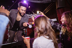 Male singer holding mic by female fan during performance. At nightclub Stock Photos