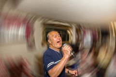 Male singer holding microphone. Male singer in action hitting a high note Royalty Free Stock Photography