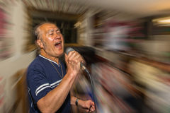 Male singer holding microphone. Male singer in action hitting a high note Royalty Free Stock Image