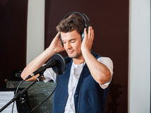 Male Singer Listening Carefully To Music Through. Young male singer listening carefully to music through headphones in recording studio stock images