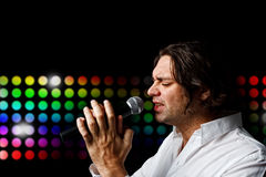Male singer with microphone. Male singer in white clothes with microphone on different light background Royalty Free Stock Photos