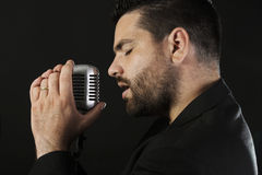 Male singer with microphone. Portrait of male  singer  with old fashioned microphone against black background Royalty Free Stock Photography