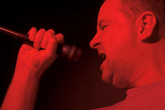 Male singer with microphone. Side portrait of middle aged male singer with microphone performing under red light Royalty Free Stock Photos