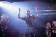 Male singer with musicians performing during music festival Royalty Free Stock Image