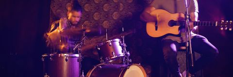 Male singer performing with drummer in nightclub. Male singer performing with drummer in illuminated nightclub Stock Image