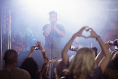 Male singer performing in front of crowd at nightclub. During music festival Stock Photo