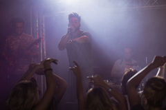 Male singer performing in front of fans at nightclub Royalty Free Stock Photo