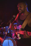 Male singer performing with guitar in night club. Close up of male singer performing with guitar in night club Royalty Free Stock Photography