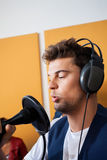 Male Singer Performing While Holding Microphone. Young male singer performing while holding microphone in recording studio Stock Photo