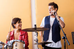 Male Singer Performing While Looking At Female. Happy male singer performing while looking at female drummer in recording studio Royalty Free Stock Photos