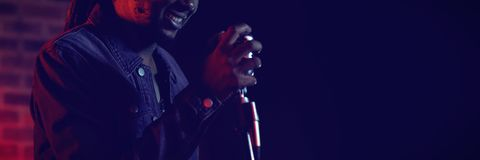 Male singer performing in popular music concert. Smiling male singer performing in popular music concert Stock Photo