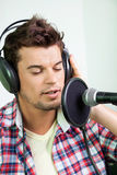 Male Singer Performing In Recording Studio. Closeup of young male singer performing in recording studio Royalty Free Stock Images