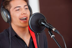 Male Singer Performing In Recording Studio. Handsome male singer performing in recording studio Stock Photos