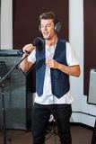 Male Singer Performing In Recording Studio. Young male singer performing in recording studio Stock Photography