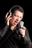 A male singer performing a song. Isolated on black background Royalty Free Stock Photos