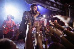 Male singer performing on stage by crowd at nightclub Royalty Free Stock Images