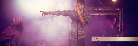 Male singer performing on stage. During music festival at nightclub Royalty Free Stock Images