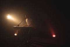 Male singer playing piano in illuminated nightclub. Full length of male singer playing piano in illuminated nightclub Royalty Free Stock Photos