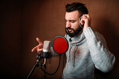 Male singer recording a song in music studio. Vocalist in headphones against microphone. Audio recording. Professional digital sound technologies Stock Images
