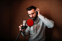 Male singer recording a song in music studio. Vocalist in headphones against microphone. Audio recording. Professional digital sound technologies Stock Photography