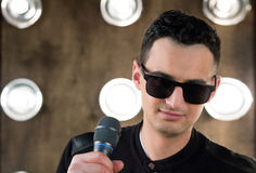 Male singer in sunglasses with microphone performing in projecto. Male singer of rock or pop music dressed in black and sunglasses with microphone performs on Royalty Free Stock Photos
