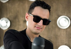Male singer in sunglasses with microphone performs in projectors. Male singer of rock or pop music dressed in black and sunglasses with microphone performs on Royalty Free Stock Images