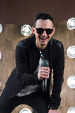Male singer in sunglasses with microphone singing in projectors. Male singer of rock or pop music dressed in black and sunglasses with microphone performs on Royalty Free Stock Photos