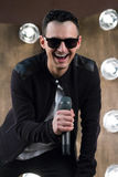 Male singer in sunglasses with microphone sings in projectors li. Male singer of rock or pop music dressed in black and sunglasses with microphone performs on Royalty Free Stock Photos