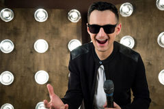 Male singer in sunglasses performing on scene in projectors ligh Stock Photos