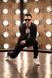 Male singer in sunglasses sings on scene in projectors lights. Male singer of rock or pop music dressed in black and sunglasses with microphone performs on scene Royalty Free Stock Photography