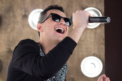 Male singer in sunglasses sings on scene in projectors lights. Male singer of rock or pop music dressed in black and sunglasses with microphone performs on scene Stock Image