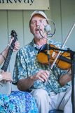 Male Singing and Playing a Violin. Roanoke, VA – September 24th: Male member of the Indian Run String Band playing a violin and singing at the Roanoke Mountain Stock Photography