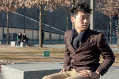 Male sitting on bench Stock Photo