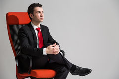 Male sitting with crossed legs. Caucasian businessman sitting on red sviwel chair with his legs crossed and looking away from the camera on grey background Stock Images
