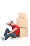 Male sitting on floor tired of moving boxes. Stock Image