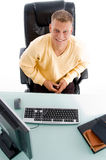 Male sitting in front of working desk Stock Images