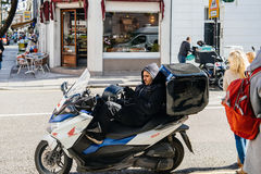 Male sitting on motorcycle using mobile phone. LONDON, UNITED KINGDOM - MAR 9, 2017: Delivery man sitting on his motorcycle moped touching the screen of the Royalty Free Stock Photos