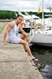 Male sitting near the yacht. Attractive muscular male sitting near the yacht Stock Photography