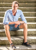 Male sitting outdoors. On stone stairs Stock Images
